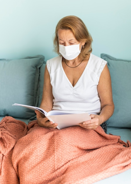 Elder woman with medical mask at home during the pandemic reading a book Free Photo