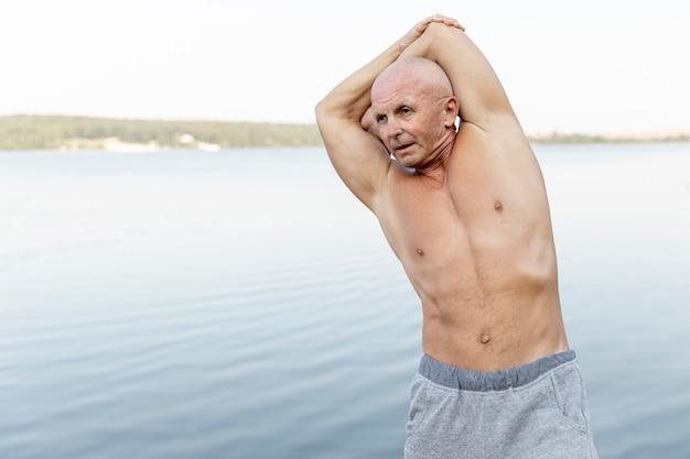 Elder working out near lake Free Photo