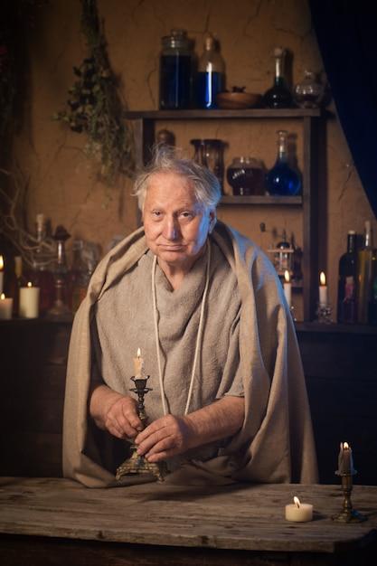 キャンドルと高齢者の錬金術師の僧侶 Premium写真
