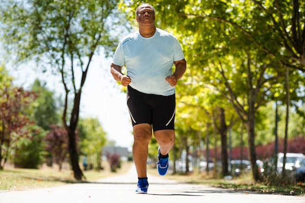An elderly black man is running in the park making a lot of effort to reduce overweight Premium Photo