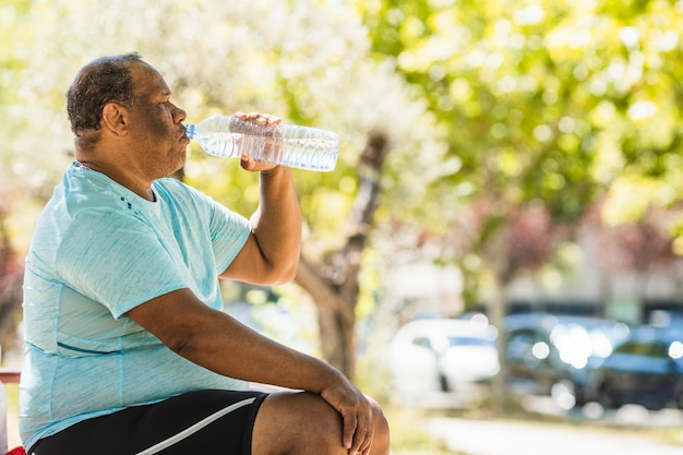 An elderly black man with overweight and morbid obesity is drinking water in the park Premium Photo
