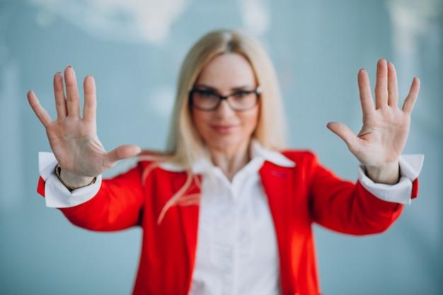 赤いジャケットで手を示す高齢者のビジネス女性 無料写真