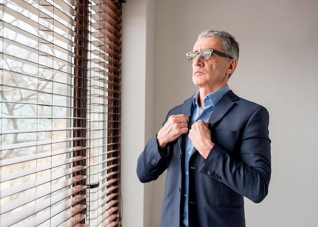 Elderly businessman looking through window Free Photo