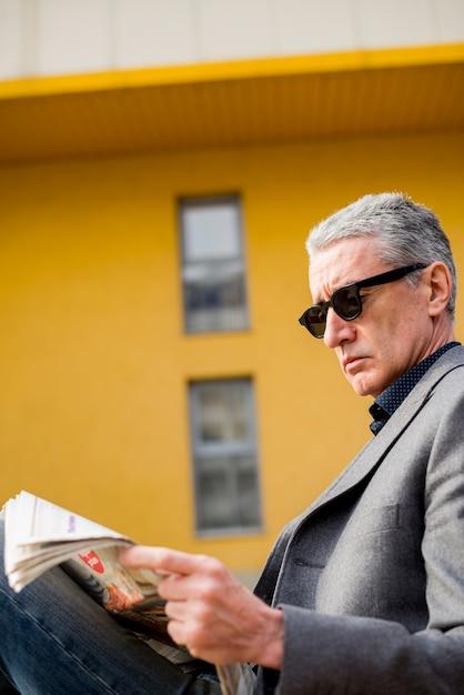 Elderly businessman reading newspaper Free Photo