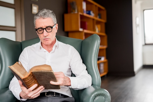Elderly businessman reading Free Photo