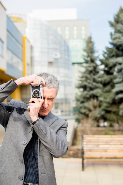 Elderly businessman taking a picture Free Photo