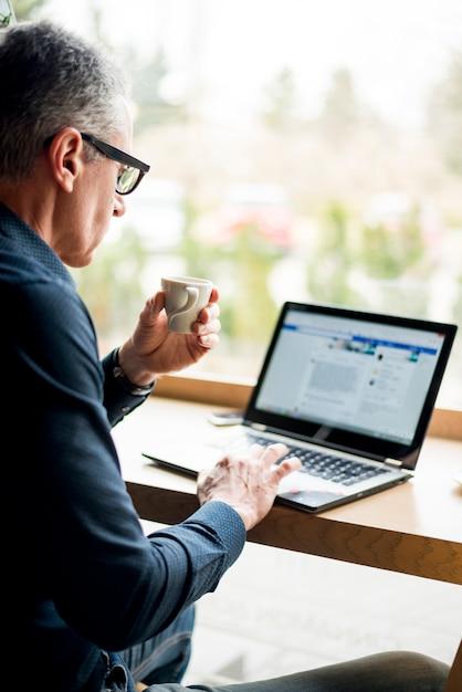 Elderly businessman working in laptop Free Photo
