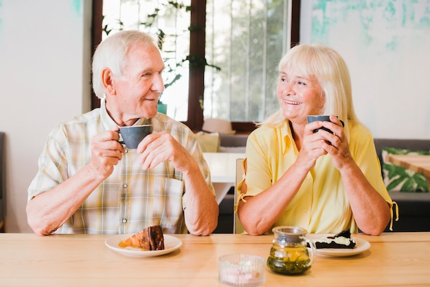 Elderly cheerful couple drinking tea and talking lively Free Photo