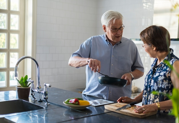 Elderly couple cooking together Free Photo