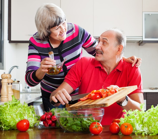 Elderly couple cooking with tomatoes Free Photo