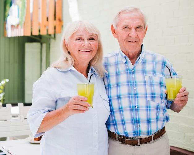 Elderly couple embracing holding glasses of juice Free Photo