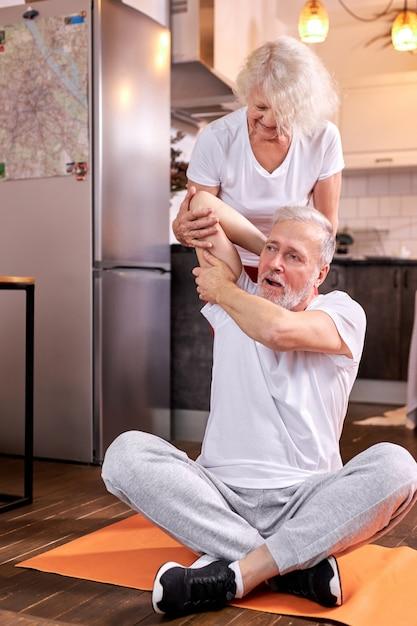 自宅で運動している老夫婦、女性は床に座って、夫がストレッチするのを手伝います。幸福、健康的なライフスタイルの概念 Premium写真