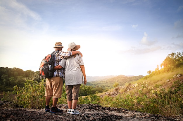 Elderly couple, hiking and standing on a high mountain, are happy in retirement. Premium Photo
