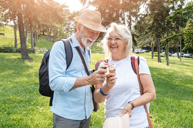 Elderly couple holding ice cream in hand Free Photo