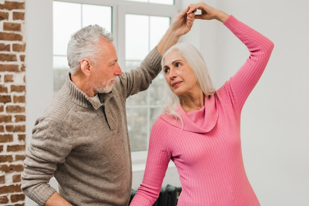 Elderly couple at home dancing Free Photo