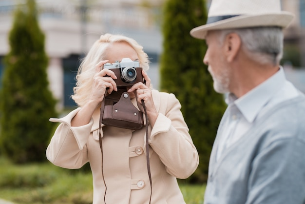 An elderly couple is sitting on the edge of a flower bed Premium Photo