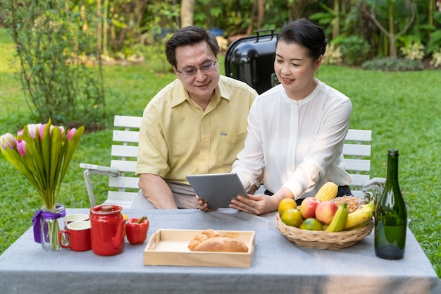 An elderly couple is sitting watching the screen tablet Premium Photo