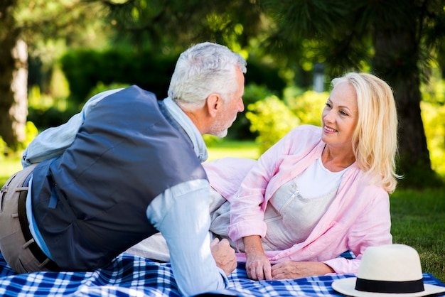 Elderly couple laying on a blanket Free Photo