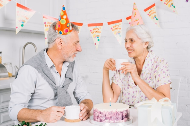 Elderly couple looking at each other while having cup of coffee during birthday party Free Photo