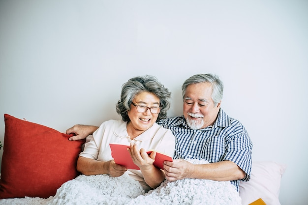 Elderly couple lying on the bed and reading a book Free Photo
