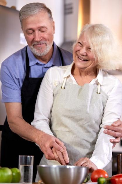 Пожилая пара готовит овощной салат на кухне, седой красавец помогает жене с приготовлением пищи, собираясь на здоровый завтрак. сосредоточиться на руках Premium Фотографии