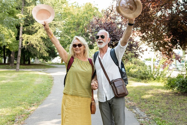 Elderly couple raising their hats in the air Free Photo