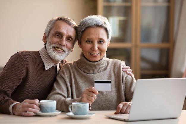 Пожилая пара делает покупки в интернете Premium Фотографии