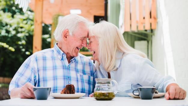 Elderly couple sitting head to head drinking tea Free Photo