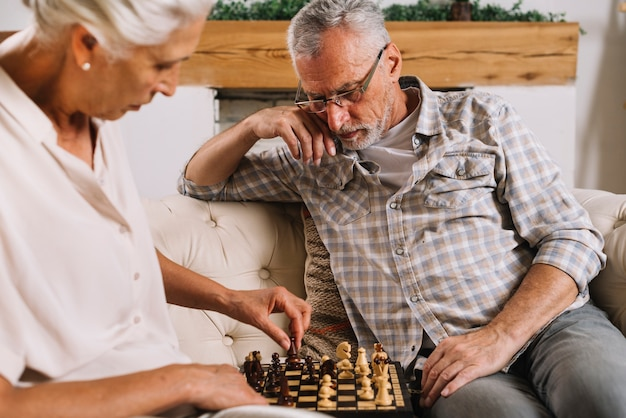 An elderly couple sitting on sofa playing chess Free Photo