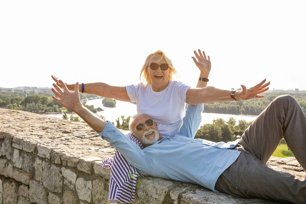Elderly couple stretching their arms in the air Free Photo
