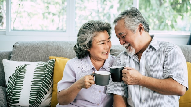 Elderly couple talking together and drinking coffee or milk Free Photo