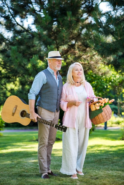 Elderly couple with guitar and picnic basket Free Photo