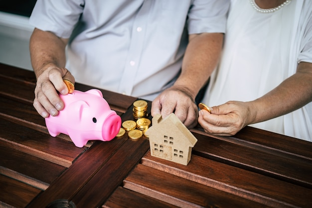 Elderly couples talking about finance with piggy bank Free Photo