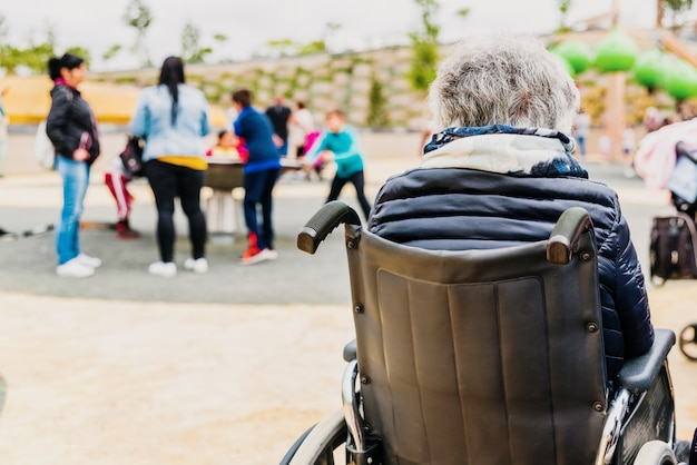 Elderly disabled woman sitting back to back in a wheelchair in a playground. Premium Photo