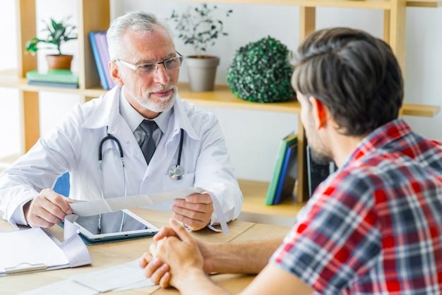Пожилой врач, слушая молодого пациента Premium Фотографии