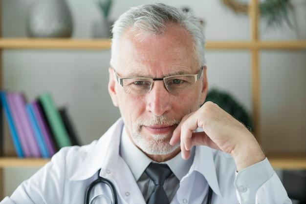 Пожилой врач, думающий в офисе Бесплатные Фотографии