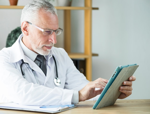 Пожилой врач, используя планшет в офисе Бесплатные Фотографии