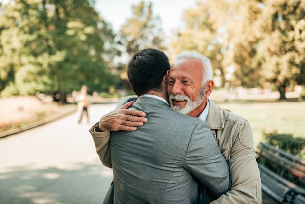 Elderly father and adult son hugging in the park. Premium Photo