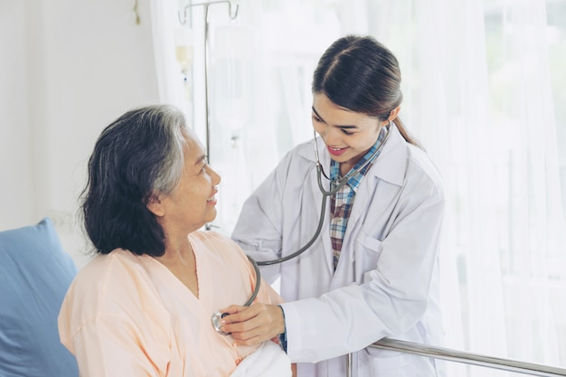 Пожилая женщина улыбается с врачом и посещение старшей пациентки в больничной палате Бесплатные Фотографии