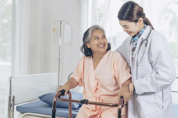 병원 병동에서 노인 환자 여자를 방문하는 젊은 여성 의사와 함께 웃고 노인 여성 무료 사진