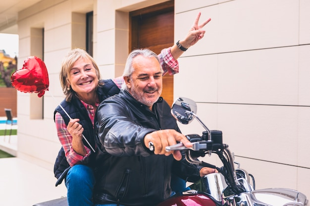 Elderly happy couple riding motorcycle Free Photo