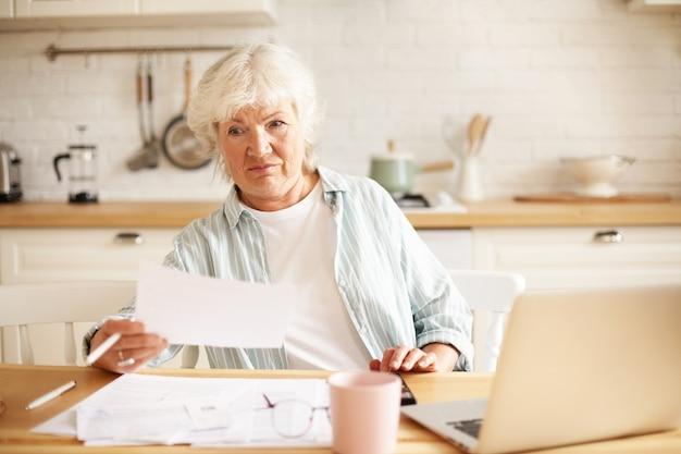 열린 노트북과 서류를 테이블에 놓고 부엌에 앉아 회색 머리를 가진 노인 주부 무료 사진