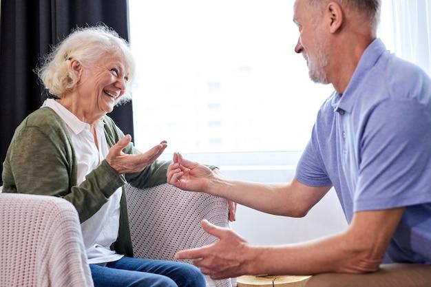 年配の夫は彼の妻のために驚きました、彼女を喜ばせてください、白髪の男は年配の嬉しい驚きの女性に贈り物を贈っています、リングを与えてください Premium写真
