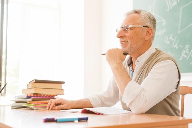 Elderly lecturer sitting at desk in auditorium Free Photo