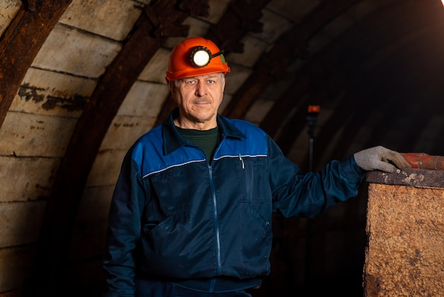 An elderly man dressed in work overalls and a hard hat is standing near the old caravan. Premium Photo