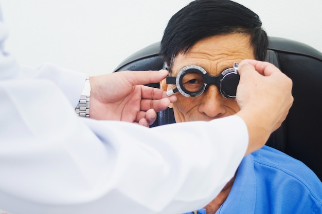 Elderly man having hes eyes examined by an eye doctor on a testing tool in modern clinic Premium Photo