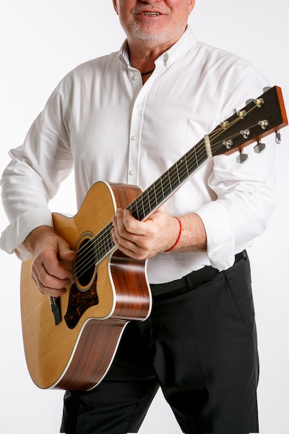 An elderly man is playing a guitar isolated Premium Photo