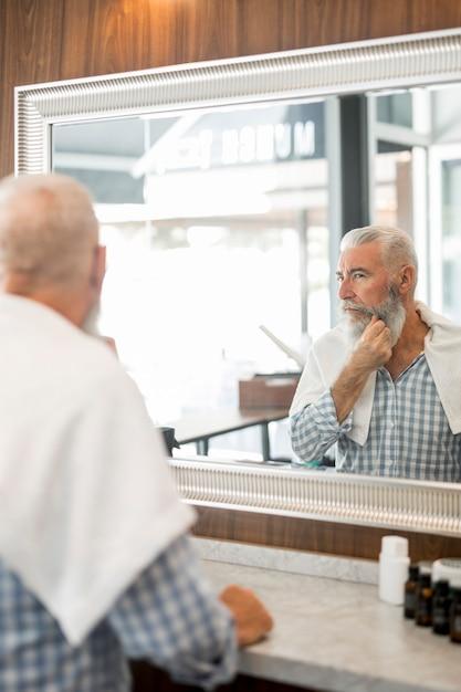 Elderly man looking at mirror in barber shop Free Photo