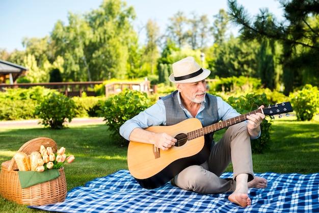 Elderly man playing on guitar Free Photo