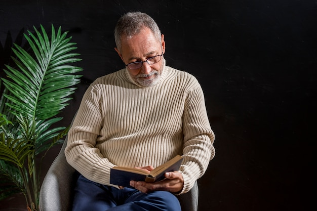 Elderly man reading book Free Photo